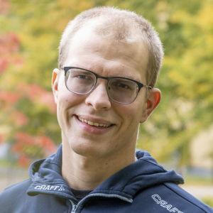 Antti Latikka hymyilee ruskan värittämässä puistossa.