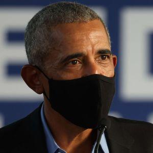 USA:s tidigare president Barack Obama talar med händerna i luften. Han har ett svart munskydd på sig.