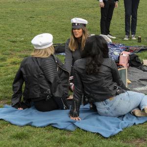 Studenter på picknick på gräsmatta.