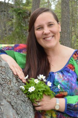 Laura Leppänen, en dam med färggrann klänning och en bukett vitsippor i handen, lutar sig mot en sten.