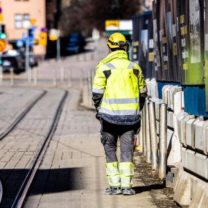 Rakennustyöläinen kävelee kadulla.