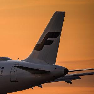 Ett Finnairplan flyger under en solnedgång. Himlen är orange.