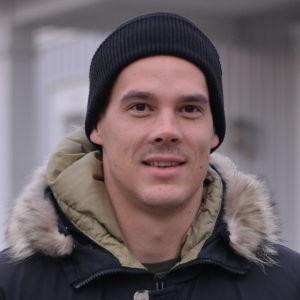 Nico Rönnberg står utanför ett hus.