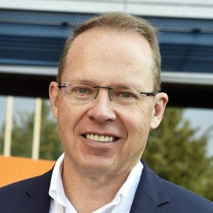 Heikki Malinen, en äldre man i blå kostym med glasögon. Han står framför en orange skylt med texten Posti.