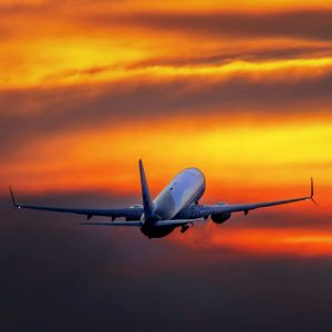 Flygplan lyfter, morgonrodnad i bakgrunden.