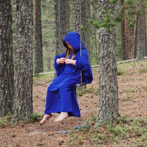 Siniseen kaapuun pukeutunut tyttö istuu keinussa metsässä.