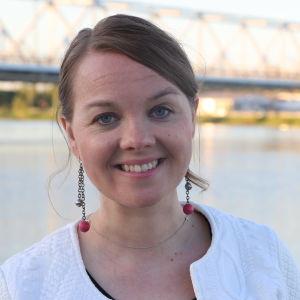 Katri Kulmuni står iklädd vit tröja nära vatten. Hon ler.
