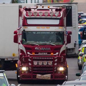En polisbil som eskorterar en röd lastbil.