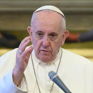 En äldre man i vit dräkt och vit huvudbonad samt ett stort metallkors på bröstet. Påven Franciskus i Vatikanen den 17 juni 2020.