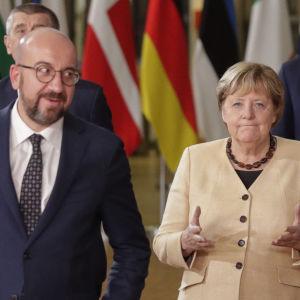 Charles Michel, Angela Merkel och Emmanuel Macron står framför en rad flaggor.