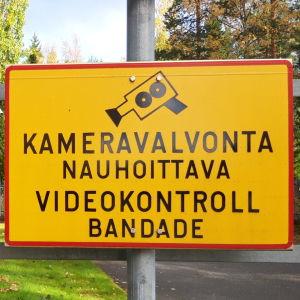 Skylt om övervakningskamera vid Polishuset i Karleby. Texten på skylten lyder: Kameravalvonta nauhoittava videokontroll bandande.