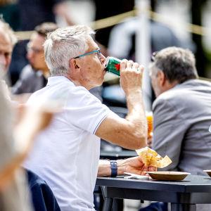 Två personer sitter vid ett bord och äter på en uteservering.