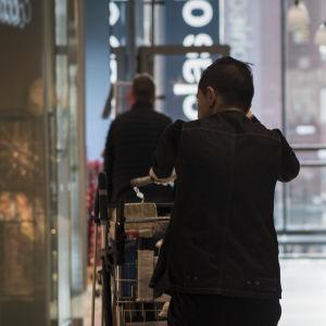 En man knuffar en städkärra på ett varuhus. I bakgrunden syns en glasvägg.
