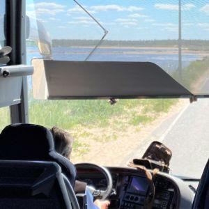 Vy genom framfönstret i en buss. Asfaltsväg med vatten på båda sidor.