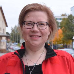 En kvinna i Röda Korset-jacka och glasögon.