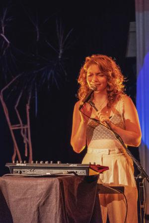 Ung kvinna står på scen och sjunger i mikrofon, i bakgrunden en teckning i blåa toner som reflekteras på ett skynke. I förgrunden ett piano med krukväxt på.