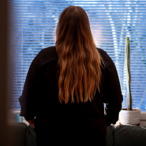 En anonym kvinna står med ryggen vänd mot kameran i ett vardagsrum.