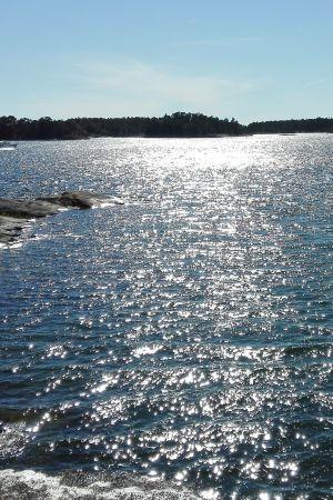 Solen glimmar i havet utanför Modermagan i Ekenäs skärgård.