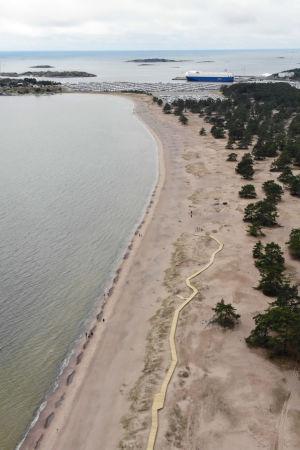 Ett flygfoto över en strand där man ser havet på ena sidan och skogen på andra. I sanden har ett promenadstråk i trä byggts. Uppe i bild syns en hamn med ett fartyg.