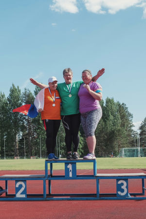 Kolme naista tuulettavat palkintokorokkeella urheilukentällä, kaulassaan mitalit.