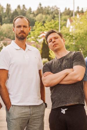 Modernit miehet seisovat vierekkäin vehreällä kadulla katsoen kameraan.