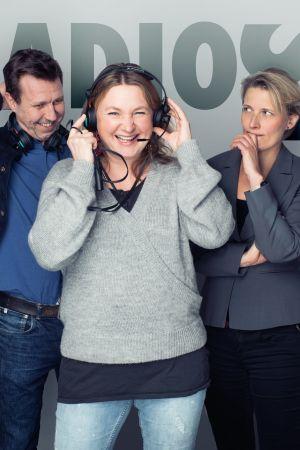 Radio Stagen tekijät seisovat harmaan seinän edessä, keulahahmo pitää kuulokkeita korvillaan.