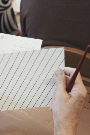 Käsi pitelee mustekynää ja viivoitettua paperia.