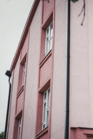 Del av gammalt stenhus med chockrosa fasad.