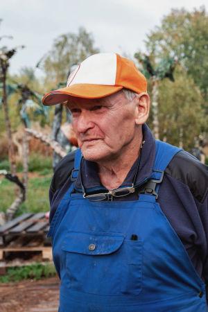 Lippalakkipäinen vanhempi mies seisoo veistospuiston edessä.
