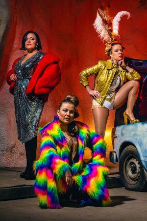 Viisi naista poseeraa auton ympärillä värikkäissä vaatteissa.