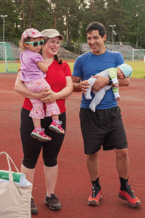Mies ja nainen seivovat hymyillen kesällä urheilukentällä, pieni lapsi ja vauva sylissään.