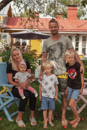Viisihenkinen perhe puutarhassa omenapuun alla, taustalla keltainen puutalo