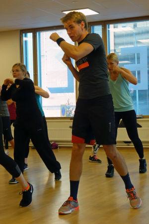 Mikael Lindgren tränar bodycombat i grupp i en konditionssal i Esbo.