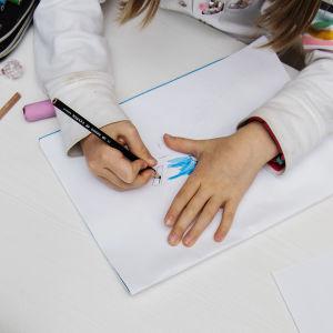 Kuvassa koululainen piirtää.