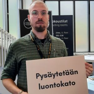 """En man håller i en skylt där det står """"Pysäytetään luontokato"""" (översättning: """"Låt oss stoppa förlusten av biologisk mångfald"""")"""