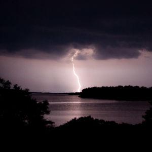 Salama valaisee tumman taivaan horisontissa