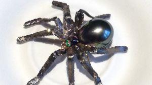En brosch formad som en spindel. Smyckeskonst med tahitipärlor, guld, safirer, smaragd och diamanter.
