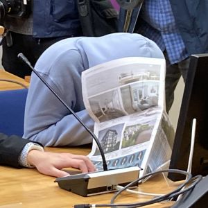 Den åtalade, som skyddar sitt ansikte med en tidning, och hans advokat sitter i Birkalands tingsrätt.