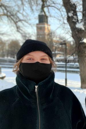 Amanda Holm och Aare Kiviranta, två ungdomar med svarta munskydd står vid ett snöigt torg med Åbo Domkyrka och Katedralskolan i bakgrunden.