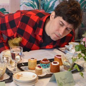 En man i rutig skjorta sitter bakom ett bord och tittar på en bricka med runebergstårtor.