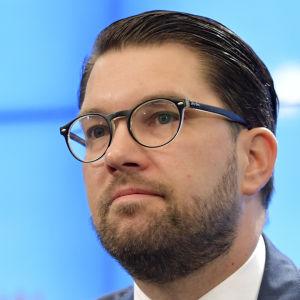 En mörkhårig man i glasögon och kostym sitter framför en mikrofon.