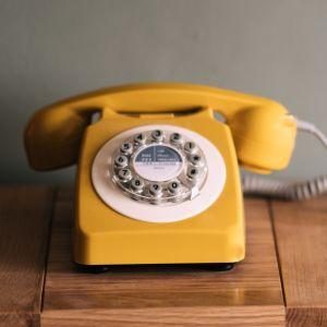 En gul trådtelefon på ett bord.
