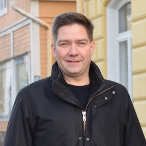 En man står på gågatan i Ekenäs. Han tittar in i kameran och ler lite.