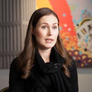Statsminister Sanna Marin sitter på en stol och intervjuas. I bakgrunden syns en färggrann tavla och Marin tittar lite förbi kameran då hon talar med intervjuaren.