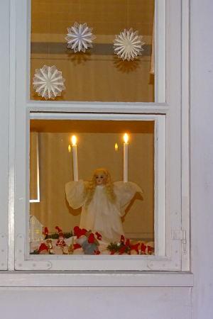 Ett fönster dekorerat med julprydnader i ett trähus