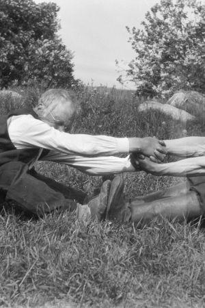 """Två män leker leken """"vetukapul"""", som är en slags dragkamp. Bilden är tagen 1929 i Strömfors, Kungsböle."""