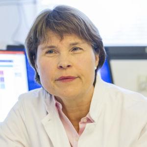 En kvinnlig läkare tittar åt sidan medan hon fotograferas framifrån. I bakgrunden syns en dator.