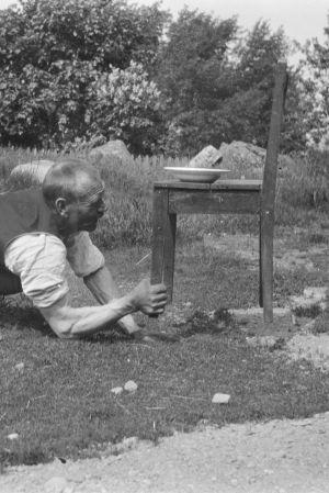 En man lyfter med sin ena hand en stol som har en tung tallrik på sig. Bilden är tagen 1929 i Kungsböle, Strömfors.