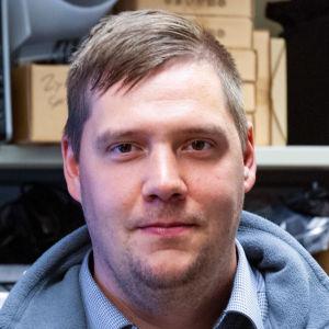 En man framför hyllor med datorkomponenter.