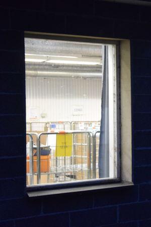 Två fönster i Hangö postterminal genom vilka man ser att verksamheten ligger nere.